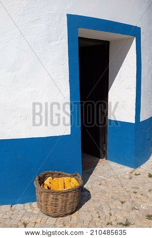 Detail of the entrance of a typical Portuguese windmill with a basket full of corn cobs