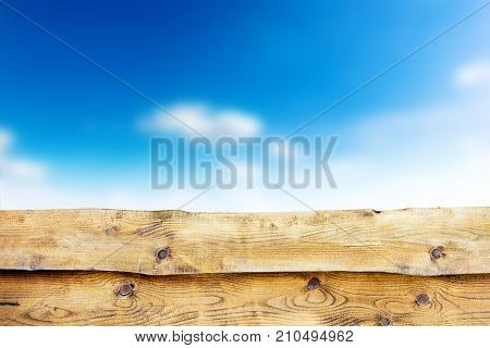 Wooden fence against blue sky with clouds background