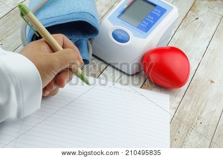 Hand is writing on blank empty paper with blood pressure monitor meter and heart shape symbol on wooden table.