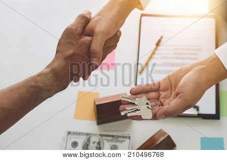 Image Of Above View, Real Estate Broker Agent And Customer Shaking Hands And Give Keys After Signing