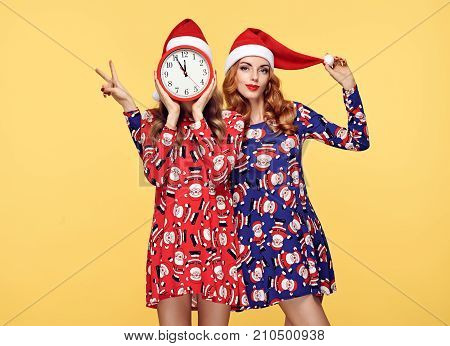 Christmas New Year. Young Woman in Santa hat Having Fun Happy Smiling with Clock. Fashion. Pretty Playful Sisters Friends. Twins in Stylish fashion Red Xmas Holiday Dress on Yellow. Christmas Colorful