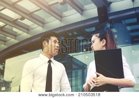 Two Business Asian People Standing In Front Of Office Building And Talking About Work.