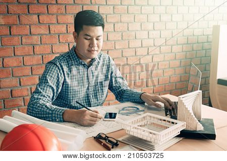 Architect asian man working in his office with sitting and typing on laptop.