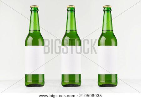 Green longneck beer bottles 500ml with blank white label on white wooden board mock up. Template for advertising design branding identity.