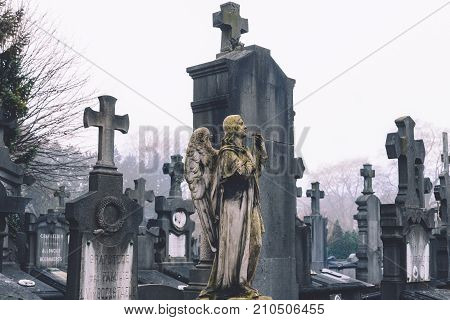 December, 29th, 2016 - Ghent, East Flanders, Belgium. Stone cemetery statue of praying angel, grave stones and crosses on Campo Santo historical old graveyard in Sint-amandsberg municipality, Gent.