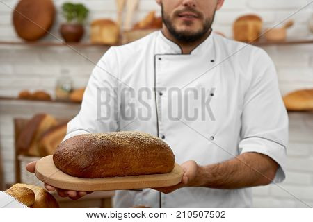 Cropped shot of a baker in uniform holding a loaf of bread posing at his bakery seller selling retail salesperson small business owner bakery baking breakfast recipe nutrition concept.