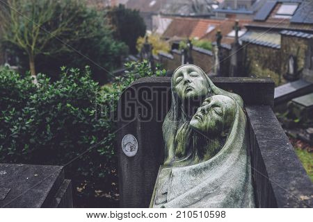 December, 29th, 2016 - Ghent, East Flanders, Belgium. Stone cemetery statues of praying man and woman on Campo Santo historical old graveyard in Sint-amandsberg municipality, Gent.