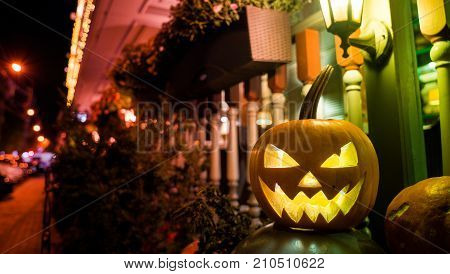 concept of halloween. A bright pumpkin with a terrible face and toothy mouth lies near the house on the street for frightening passersby at night under the light of street lamps.