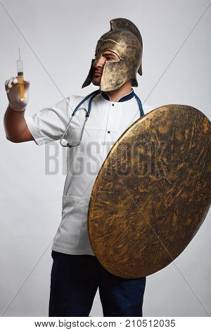 Shot of a male doctor in a helmet holding a shield and a syringe ready to vaccinate patients protective guardian healthcare soldier vitality safety prevention disease fighter concept.