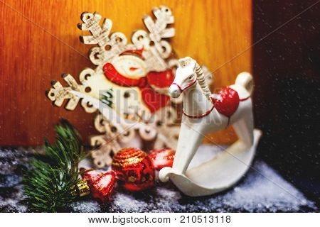 Christmas and New Year background with bright decorative ball and wooden rocking horse toy. Decorations for holiday celebration.