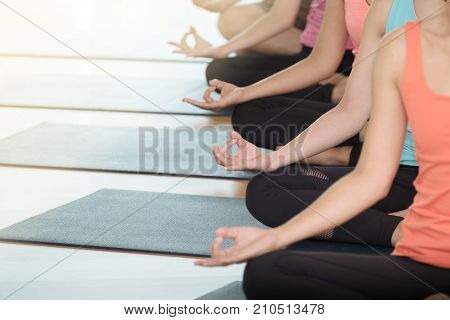 Young people praticing yoga indoors hand close up with copy space well being wellness healthy lifestyles