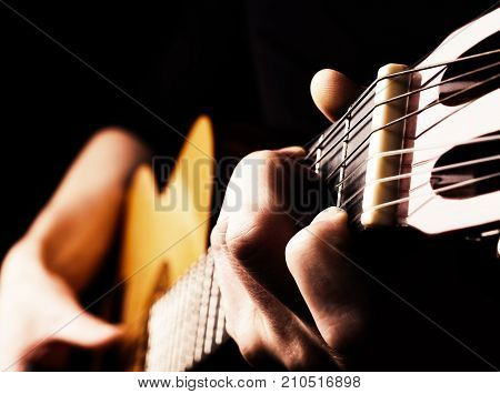 Flamenco guitar player close up playing traditional acoustic guitar concept image us as background high contrast selective focus on foreground fingers