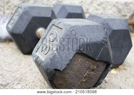 Two big rusted dumbbells in outside gym
