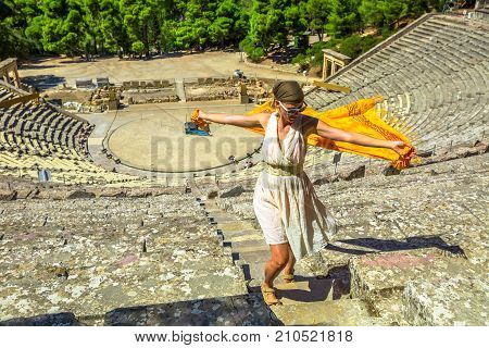 Funny woman with orange sarong and greek dress walking in Ancient Theatre Epidaurus amphitheater in Peloponnese, Greece. European travel destination. Historical heritage and landmark.