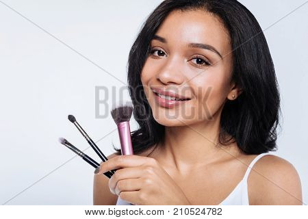 Professional makeup artist. Pretty young woman with a swarthy complexion holding a set of makeup brushes while posing against a white background