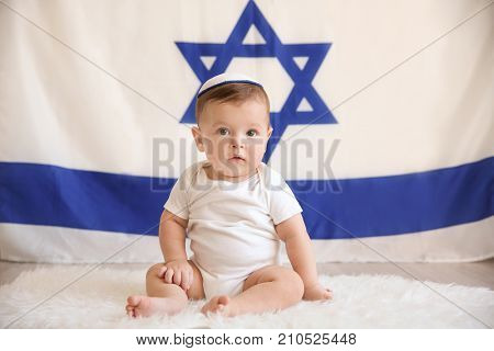 Cute baby in kippah sitting on floor against big flag of Israel