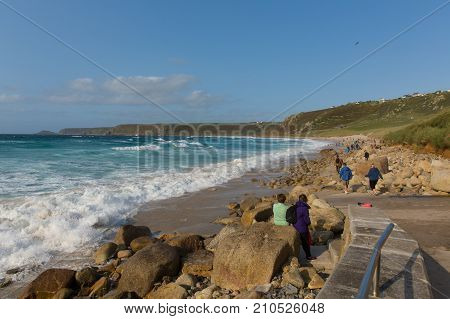 Sennon Cove beach Cornwall with people enjoying the blue sea and white waves