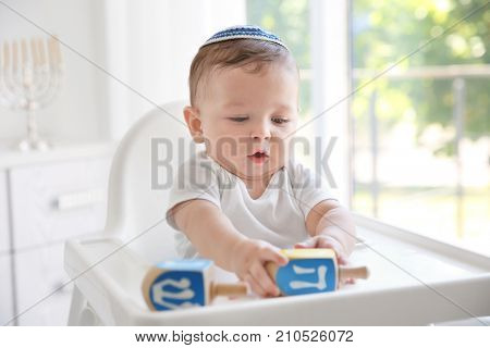 Cute baby in kippah playing with dreidels while sitting on high chair
