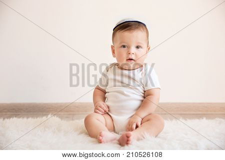 Cute baby in kippah sitting on floor at home