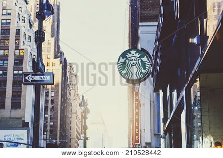NEW YORK NY - September 7th 2017: Sun flare among the streets of Manhattan shining next to a Starbucks sign (illustrative editorial)