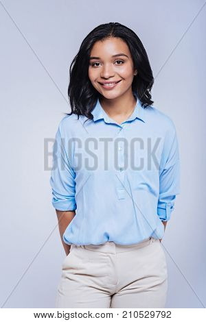 Sophisticated elegance. Charming dark-haired woman with a swarthy complexion wearing a baby blue shirt and ivory trousers and posing against a blue background