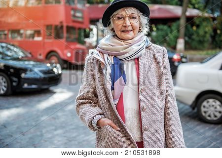 Life is great. Waist up portrait of rich old woman standing on street and smiling. Copy space