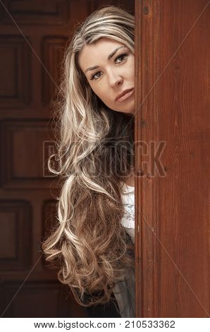 Beautiful girl peeks through the door peeking Out of Doorway. GIrl with low lighting a massive door covers half face closeup. Suspicious and attentive look.
