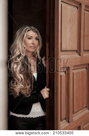 Beautiful Girl Peeks Through The Door, Peeking Out Of Doorway. Girl With Low Lighting, A Massive Doo
