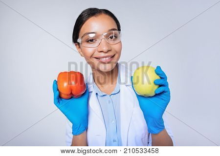Delicious and safe. Beautiful young lab worker in safety glasses showing a red bell pepper and a yellow apple, having conducted research, while standing against a blue background poster