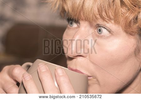 Female woman relaxing and sitting on sofa holding and sipping a hot cup of tea drink