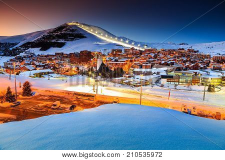 Stunning winter sunset landscape and ski resort with typical alpine wooden houses in French Alps, Alpe D Huez, France, Europe