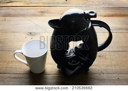 Broken Kettle with Cup on Wooden Background