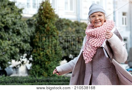 Wonderful weather for walking. Waist up portrait of joyful stylish senior lady standing outdoors and smiling. Green bushes on background. Copy space