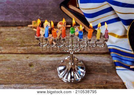 Jewish holiday hannukah prayer shawl, jewish cap and nine candle menorah