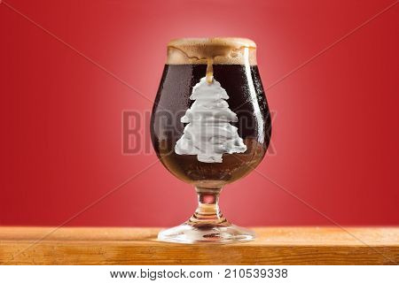 The glass of cold frothy dark beer and on christmas tree an old wooden table. Christmas, New Year concept