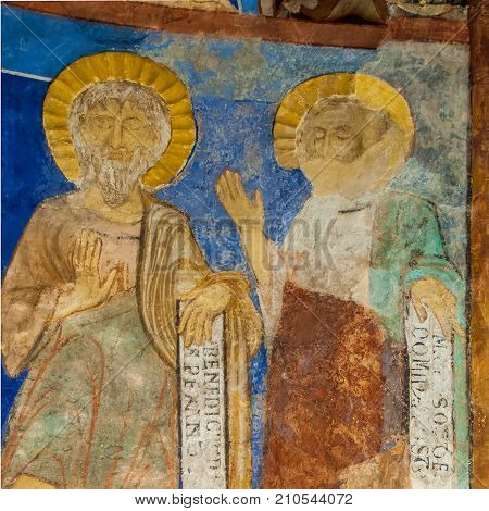 two disciples with latin texts in a medieval fresco a romanesque mural in Bjaresjo church Sweden November 6 2009