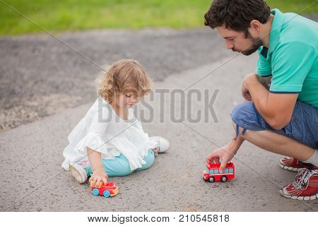 Father play with his toddler daughter in boys games. Two color cars. Family leisure. Loving caring single father. Kid playing with parent.
