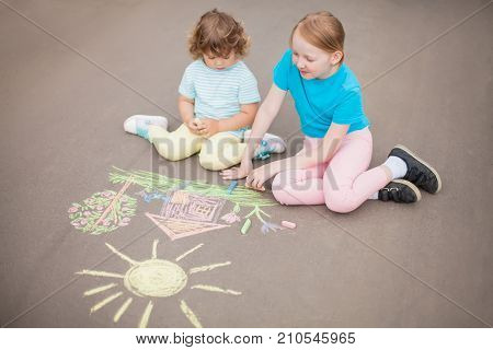Little girls sisters chalking at the asphalt. Friendship childhood elder sister. Best friends children. Drawing with color chalk. Kids in kindergarten. Preschooler leisure time. Artistic talented kids. Children's drawings.