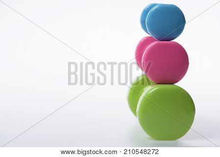 Dumbbells Made Of Blue, Pink And Green Plastic On White