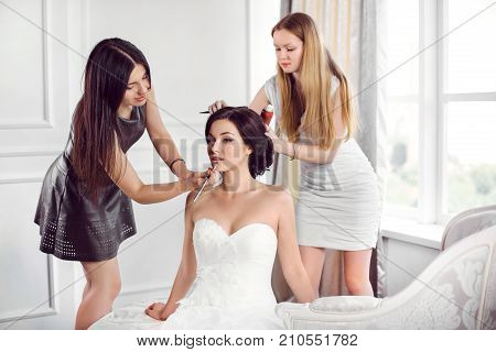 Beautiful bride perfect style. Young girl in white dress applying make-up by make-up artist and master stylist makes the bride wedding hairstyle using spray lacquer fixing indoors at home.