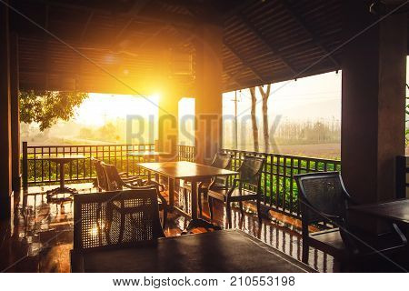 Restaurant kitchen interior concept : Empty outdoor restaurant tables at sunset light in the evening with nature view background