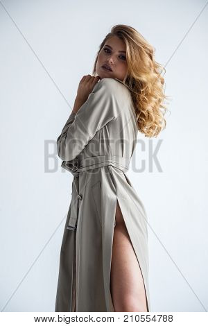 Lovely girl sexy blonde posing in a coat on a white background