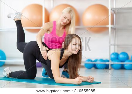 Beautiful young sporty woman smiling while exercising with her fitness trainer performing donkey kicks exercise professional fitness coach training her client at the gym aerobics sports lifestyle.
