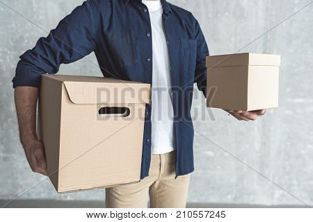 Courier service concept. Close-up of two cardboard boxes in hands of professional courier who is delivering purchases. He is standing against gray wall