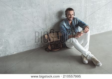 Joyful rhythm. Top view full length of cheerful man with beard is sitting on floor with bag and listening to music through headphones. He is using mobile phone with smile. Copy space in the left side