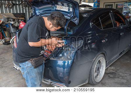 Checking A Car Taillight For Repair At Car Garage