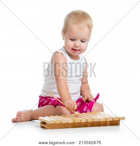 Little girl with excitement playing on xylophone isolated on white background.