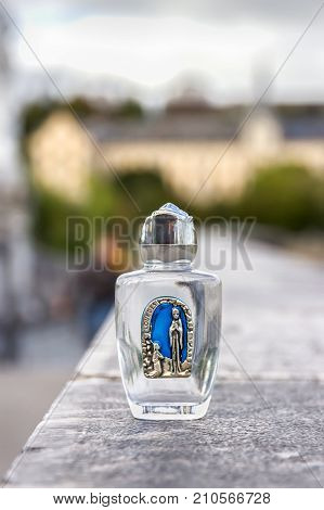 Holy water in a small bottle. Lourdes, France 2017