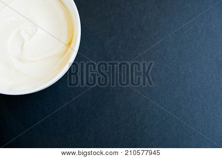 White Bowl Of Cream On Light Blue Background, Top View