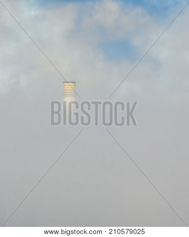 Old smokestack peeks out from morning fog